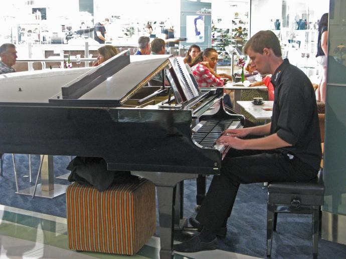 A piano player entertains the coffee drinkers and creates a pleasant atmosphere