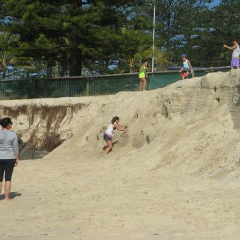 Children are having fun on the escarpment caused by erosion