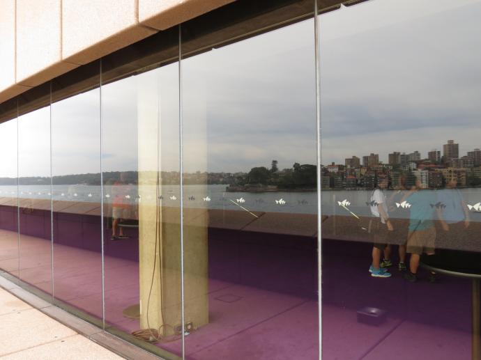 The harbour and the city reflected in the Opera House windows