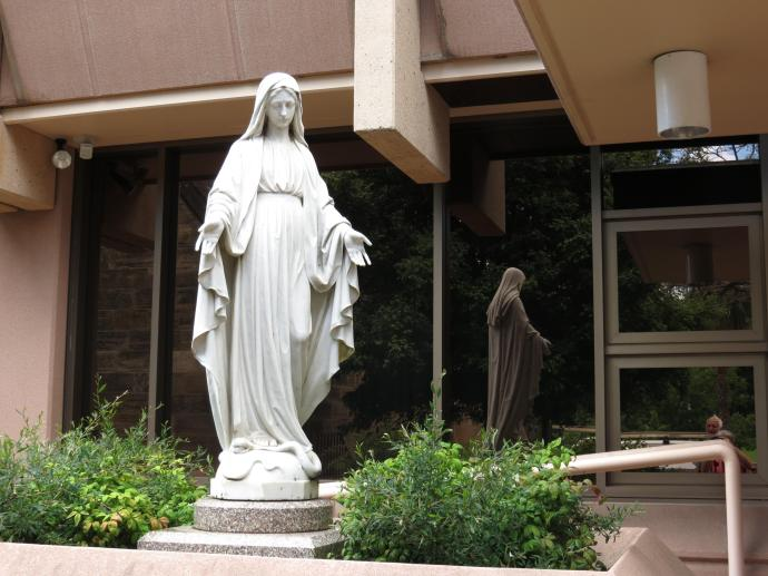 Statue of the Virgin Mary reflected in the windows of St Andrews school
