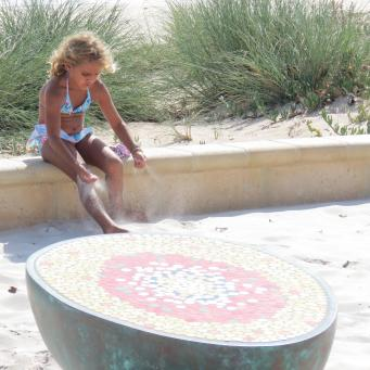 This pretty young girl is playing in the sand