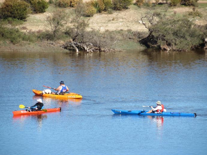 3 canoeists paddle slowly along.